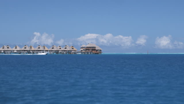 WS POV Speed boat passing by houses on stilts in tropical lagoon, Bora Bora, Society Islands, French Polynesia