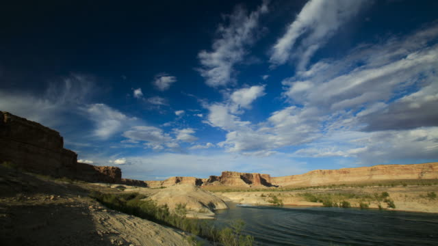 vidéos et rushes de ws t/l speed boat passing by lake powell with cloudscape / utah, usa. - lac powell
