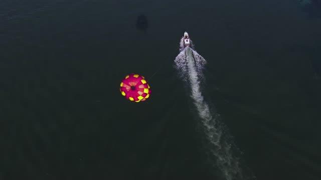 speed-boot mit fallschirm-antenne - küste stock-videos und b-roll-filmmaterial