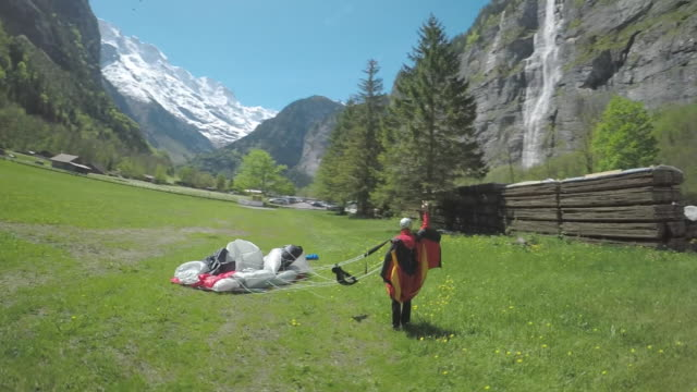 Speed drone circling wingsuit flyer standing in field