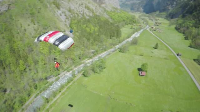 speed drone following wingsuit flyer landing in field - fallschirm stock-videos und b-roll-filmmaterial