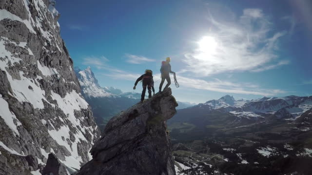 speed drone perspective of mountaineers ascending a high mountain pinnacle - esplorazione video stock e b–roll