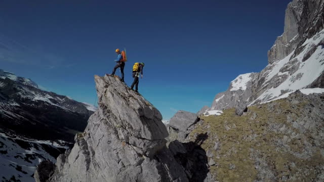 speed drone perspective of mountaineers ascending a high mountain pinnacle - ganz oben stock-videos und b-roll-filmmaterial