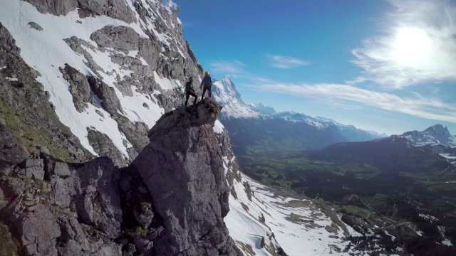 Speed drone perspective of mountaineers ascending a high mountain pinnacle