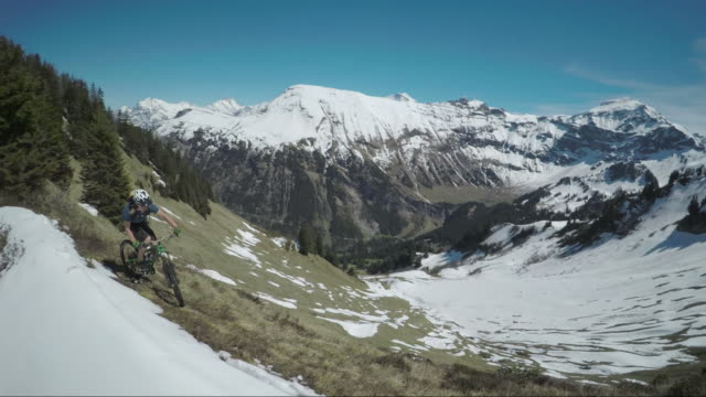 vídeos de stock, filmes e b-roll de speed drone view of mountain biker ascending ridge - snow cornice
