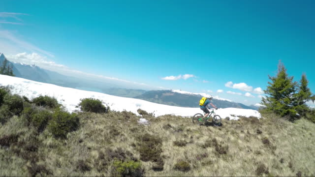 speed drone view of mountain biker ascending ridge - snow cornice stock videos and b-roll footage