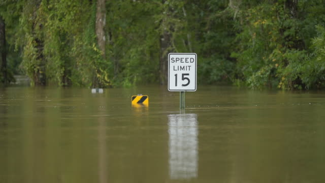 speed limit sign protruding above flowing floodwater - florida us state stock videos & royalty-free footage
