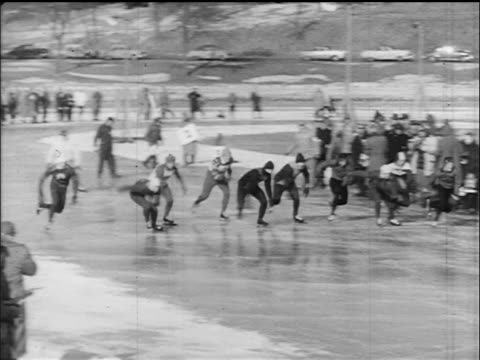 pan speed skaters taking off on frozen lake como / italy / documentary - evento storico video stock e b–roll