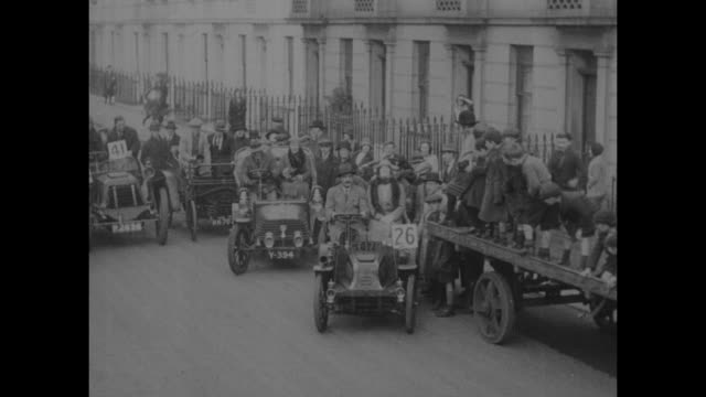 """""""speed world's oldest wheezes - london, eng. - gas chariots of yesteryear snort madly through main streets in endurance race"""" / tilt down 4 cars from... - double bed stock videos & royalty-free footage"""