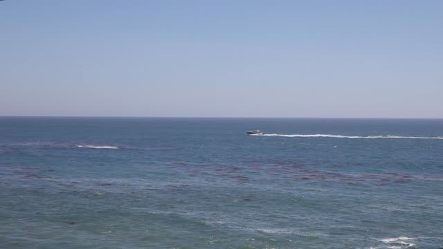vídeos y material grabado en eventos de stock de speedboat and people at the beach of laguna beach in orange county near los angeles california usa the american flag is blowing on the hill next to... - laguna beach california
