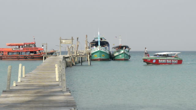 Speedboat arrive at wooden jetty with excursion ships