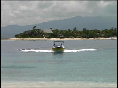 vídeos de stock e filmes b-roll de lancha chega na ilha tropical praia - barco a motor embarcação de lazer