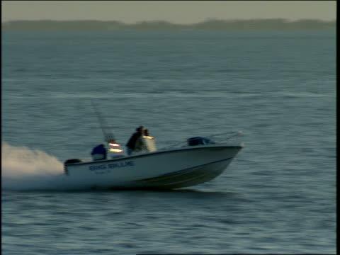 vídeos de stock, filmes e b-roll de a speedboat cruises past fishermen in tampa bay. - passear sem destino