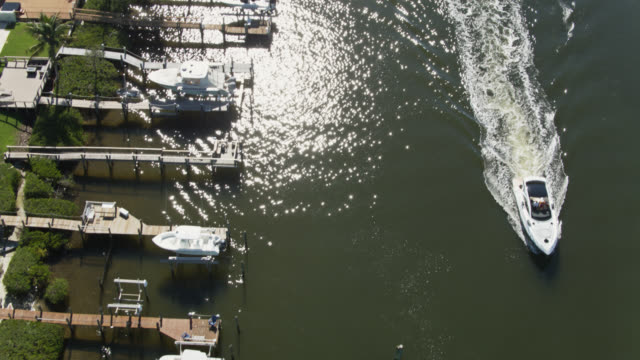 speedboat passing docks in jupiter harbour - upward tilting drone shot - jachthafen stock-videos und b-roll-filmmaterial