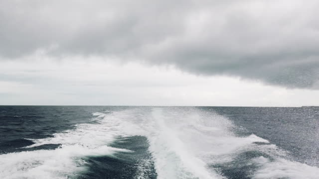 speedboat running away from storm in ocean - safety stock videos & royalty-free footage