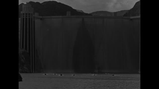vídeos de stock, filmes e b-roll de speedboats at base of enormous boulder dam / tilt down boats' race in progress / vs numerous shots of racing boats and spectators on hillsides / note... - boulder city