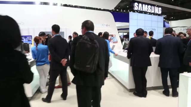 Speeded up tracking shot around the Samsung Electronics Co pavilion at the Mobile World Congress in Barcelona visitors walking around and browsing...