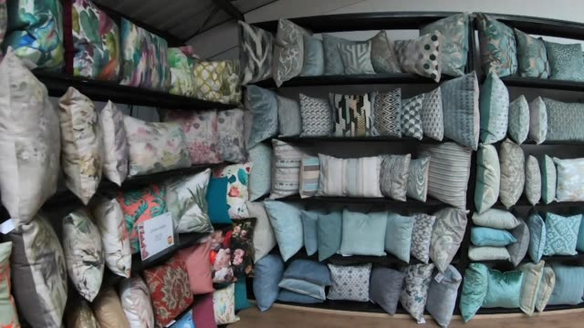 speeded up travelling shot along shelves of colourful cushions at soft furnishing factory in merseyside - veduta di interni video stock e b–roll