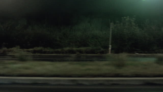 pov speeding along a highway after dark, passing illuminated shopping mall, billboards, and oncoming car traffic - side view stock videos & royalty-free footage