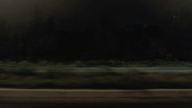 pov speeding along a highway after dark, passing illuminated storefronts, billboards, and oncoming car traffic - parallel parking stock videos & royalty-free footage