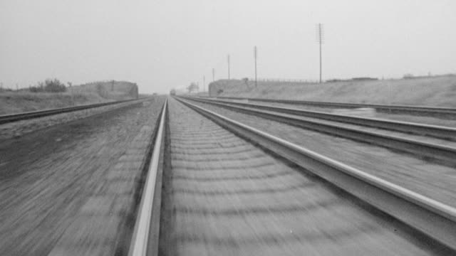 pov speeding along a train track while other trains are passing alongside / united kingdom - bahngleis stock-videos und b-roll-filmmaterial