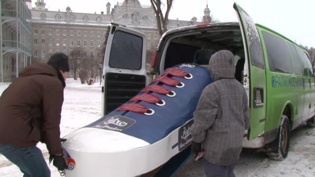 vídeos de stock, filmes e b-roll de speeding down a hill in the subzero canadian winter, in a giant shoe - that's the goal of team patroroc-amadour. quebec, quebec, canada. - 1 minuto ou mais