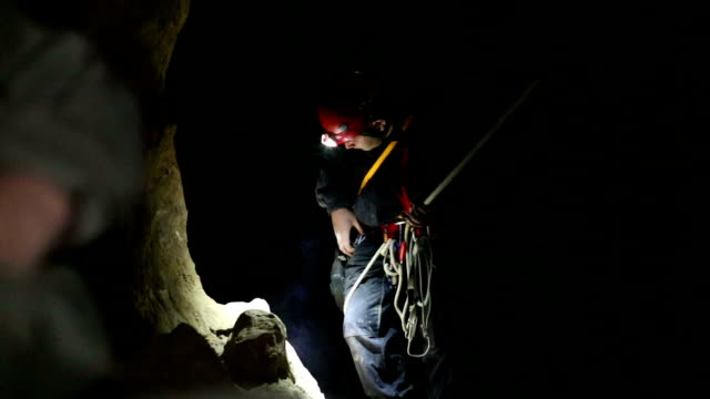 speleology explorer in a cave examining and securing a bolt on a rock 1 - cave stock videos & royalty-free footage