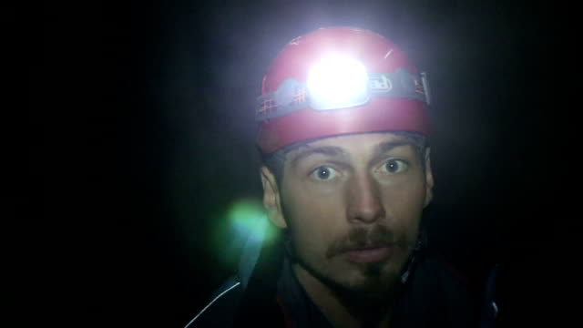 speleology explorer in a cave examining , looking around - speleology stock videos and b-roll footage