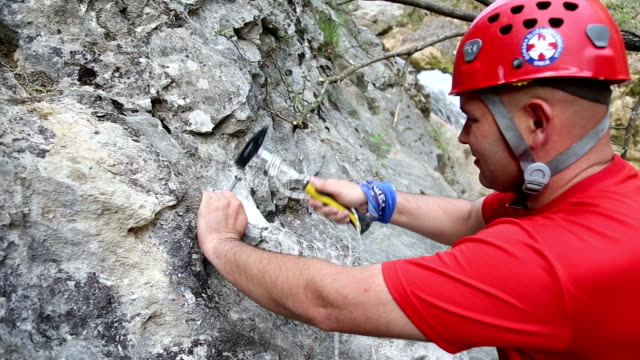 speleology team securing tourist route and putting a bolt - geologist stock videos & royalty-free footage