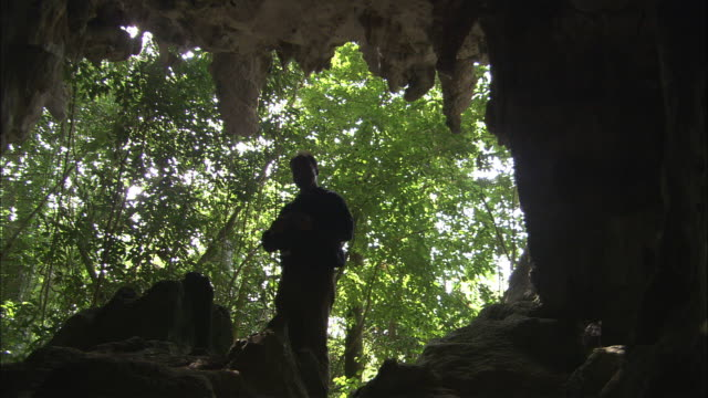A spelunker is silhouetted at the entrance of a cave as he puts on his headlamp.