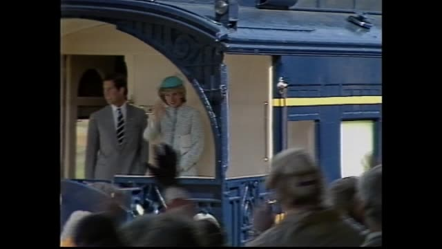 stockvideo's en b-roll-footage met crowd wait / prince charles and princess diana walk past train on platform and greet official welcoming party / children with flowers / disappointed... - 1983