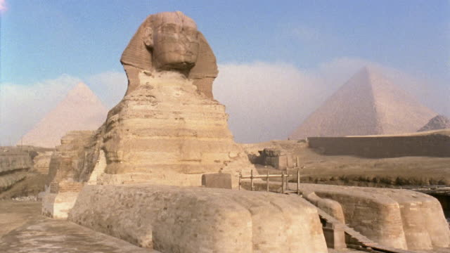 WS TL Sphinx with fog moving past Pyramid of Khafre and Great Pyramid in background/ Giza, Egypt