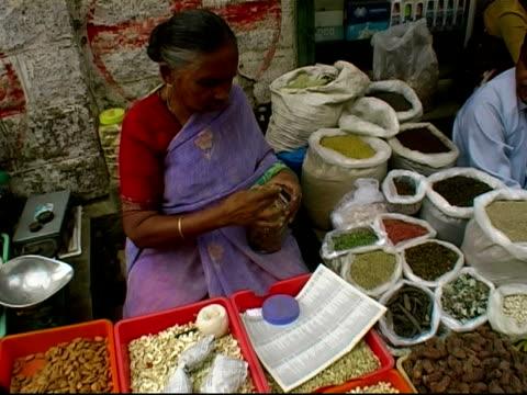 Spice vendor showing product then putting back in jar at outdoor market / Bangalore, Karnataka, India