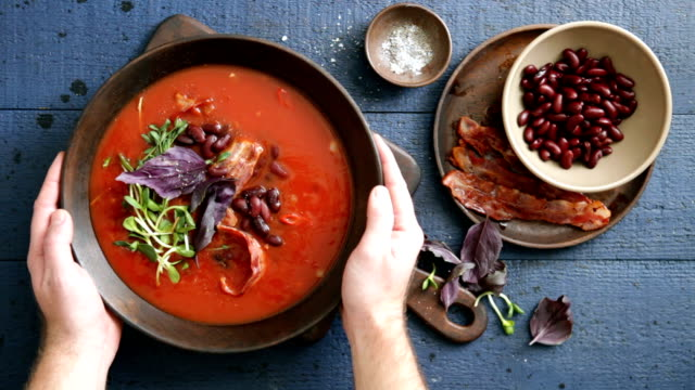 spicy tomato, bean, herb and fried bacon soup - cucina mediterranea video stock e b–roll