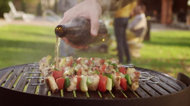 spilling birra su barbecue - grigliare video stock e b–roll