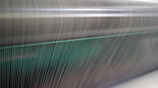 vídeos de stock, filmes e b-roll de eixo com fio branco na fábrica de jean - material têxtil