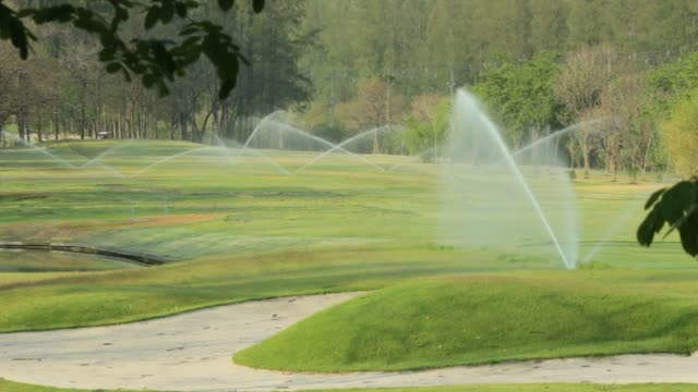 spinkling grass field. - irrigation equipment stock videos & royalty-free footage