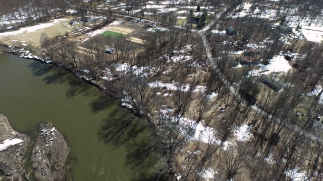 vídeos de stock, filmes e b-roll de spinning aerial shot of country setting with river in winter - new paltz