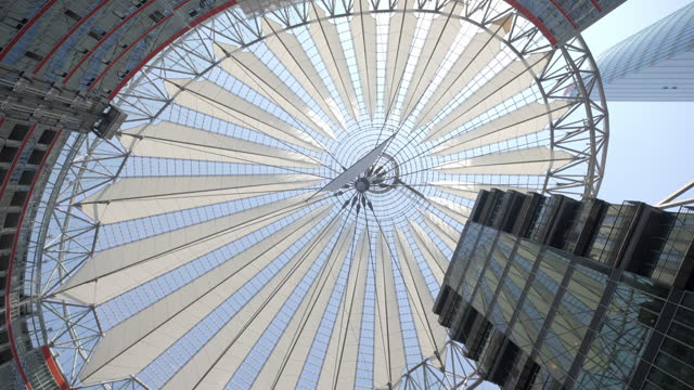 spinning and looking directly up at the canvas tent roof of the berlin sony center, with bright sunlight, soaring glass windows, and complex steel structures - large stock videos & royalty-free footage