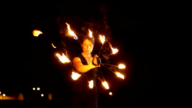 spinning around herself with fire fan - street performer stock videos and b-roll footage