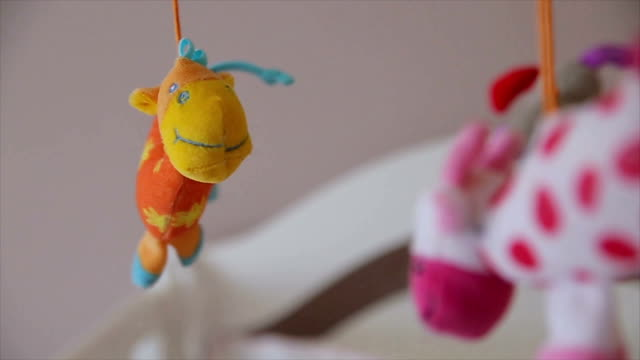 spinning baby toys above the baby's bed - group of objects stock videos and b-roll footage