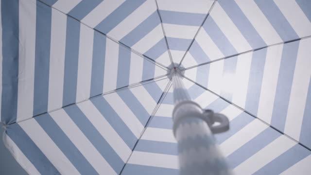 spinning beach umbrella summer mood - beach umbrella stock videos and b-roll footage