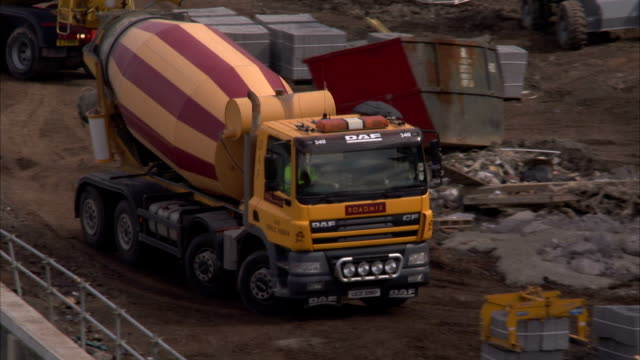 a spinning cement truck moves through a construction site in belfast's titanic quarter. available in hd. - belfast stock videos & royalty-free footage
