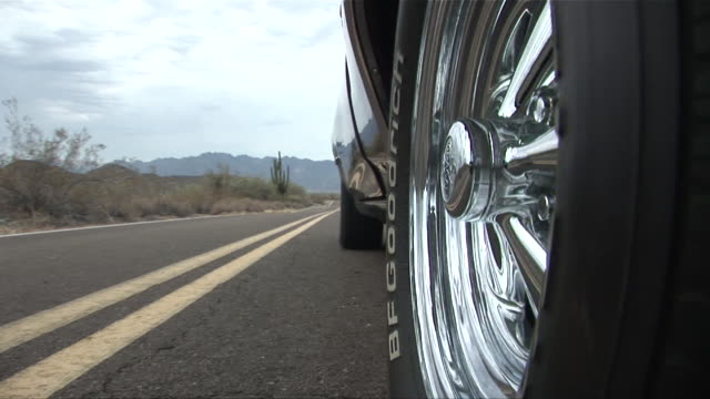 cu spinning chrome wheel of pontiac gto as it drives down desert road/ scottsdale, arizona - see other clips from this shoot 1050 stock videos and b-roll footage
