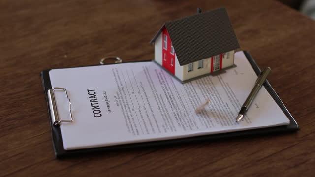 家の契約でコインを回転させる - 不動産の看板点の映像素材/bロール