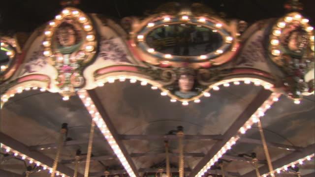 vidéos et rushes de cu spinning details of traditional carousel in amusement park at night, dallas, texas, usa - miroir ancien