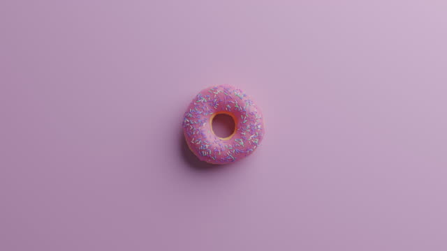 spinning donut on a pink background - two dimensional shape stock videos & royalty-free footage