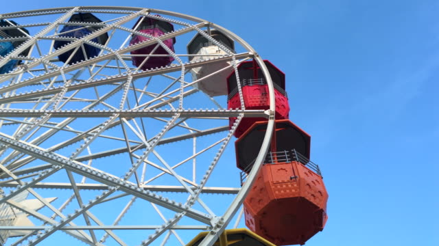 vídeos de stock e filmes b-roll de spinning ferris wheel against clear blue sky - roda gigante