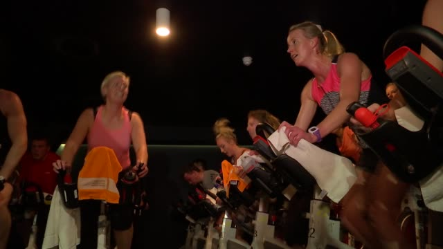 spinning fitness class; more of people taking part in spinning class at gym / participants using weights in spinning class - インドアサイクリング点の映像素材/bロール