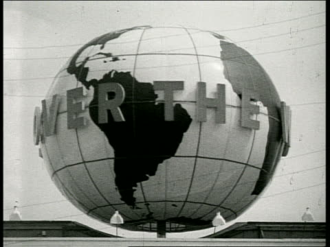 B/W spinning globe on top of building with 'All Over the World' sign